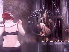 Two kinky mistresses take it out on a caged brunette slave