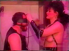 guy in rubber with weights on his balls and a mistress of couse